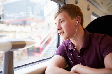 Jongen in trein met oortjes in